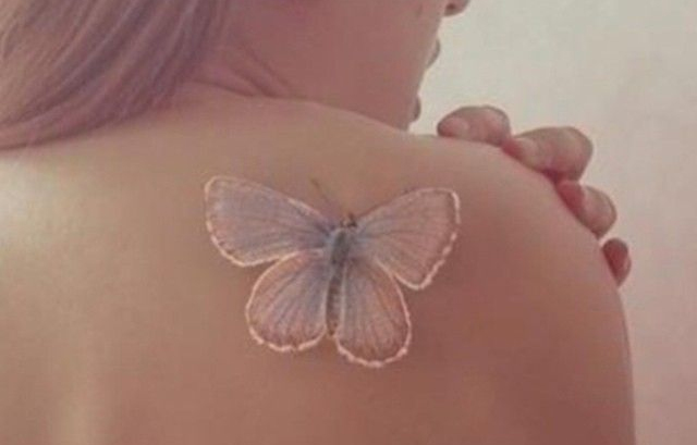 White butterfly tattoo on the shoulder