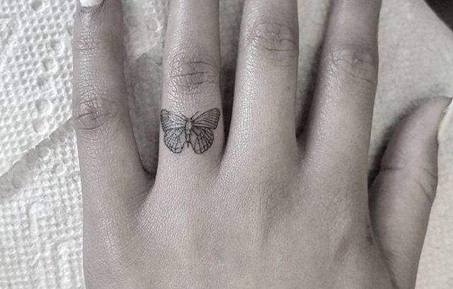 Tiny Butterfly tattoo on finger