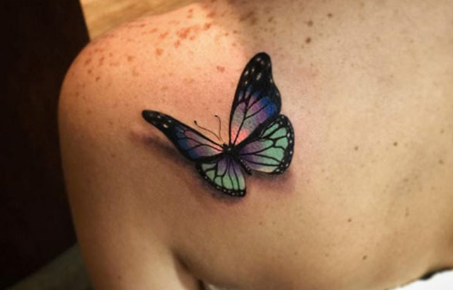 476af3d0e6574 This tattoo is done on back with only black colors which gives an  appearance that a butterfly is on a flower or it is swirling around.