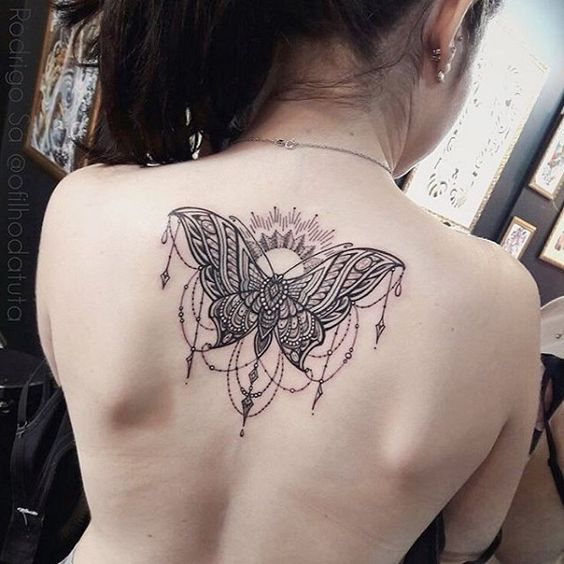 Mandala butterfly tattoo on spine