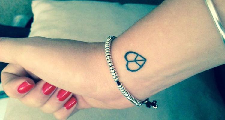 Peace symbol inside heart tattoo
