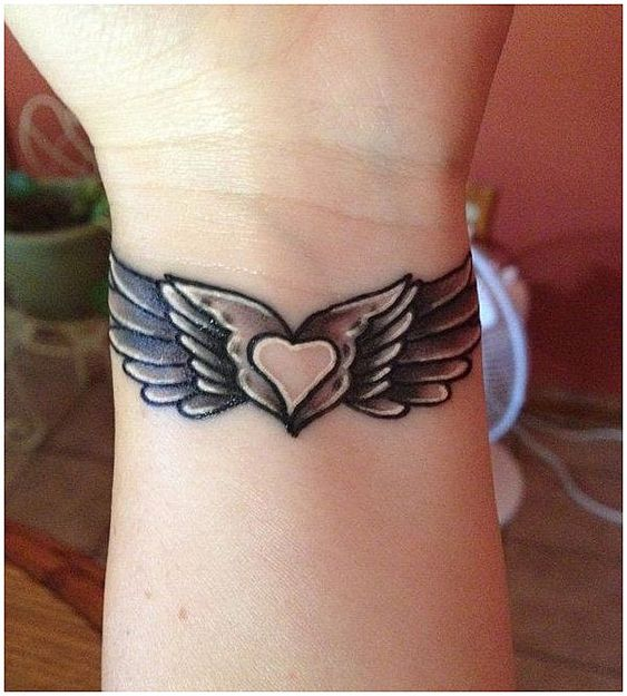 heart tattoo with wings on wrist