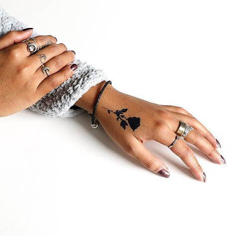Minimalist black rose tattoo on hand