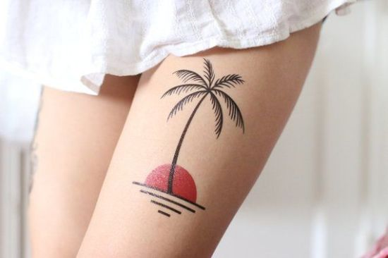 Palm with sun tattoos on girls thigh