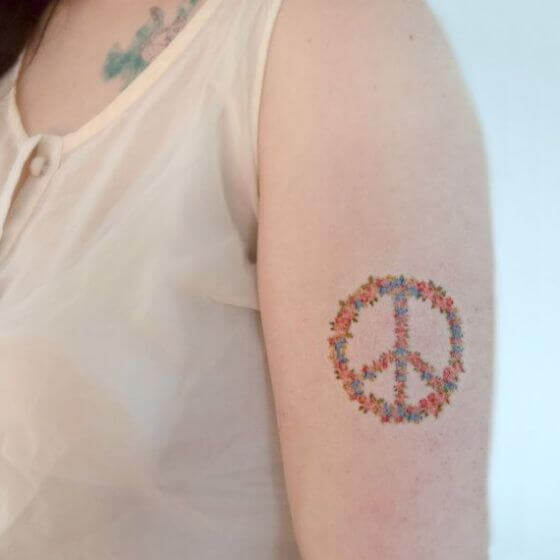 Floral peace sign tattoo for women