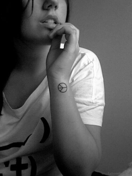 Small peace sign tattoo on Wrist
